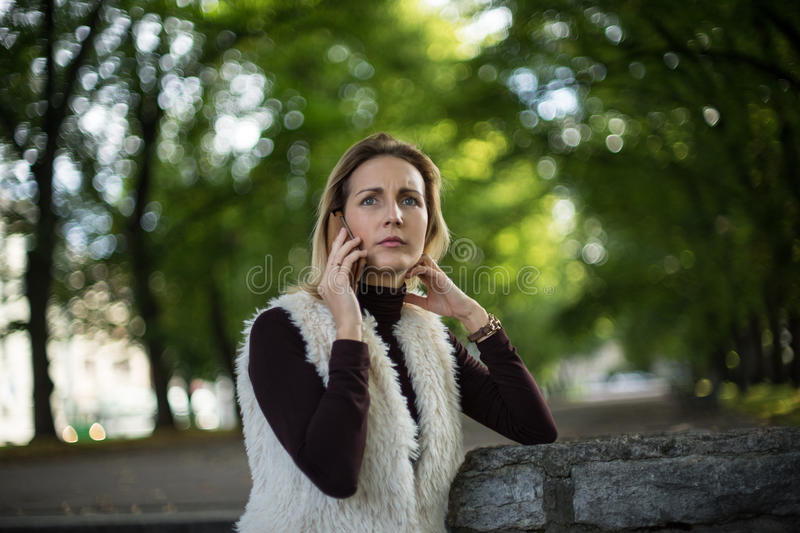 Young woman portrait in summer. Blonde girl is reading message on cell phone outside in city nature. Female with telephone. stock photography