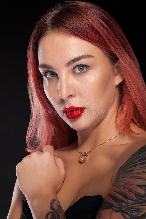 Young woman portrait with tatoo on shoulder posing in studio over black background stock photography