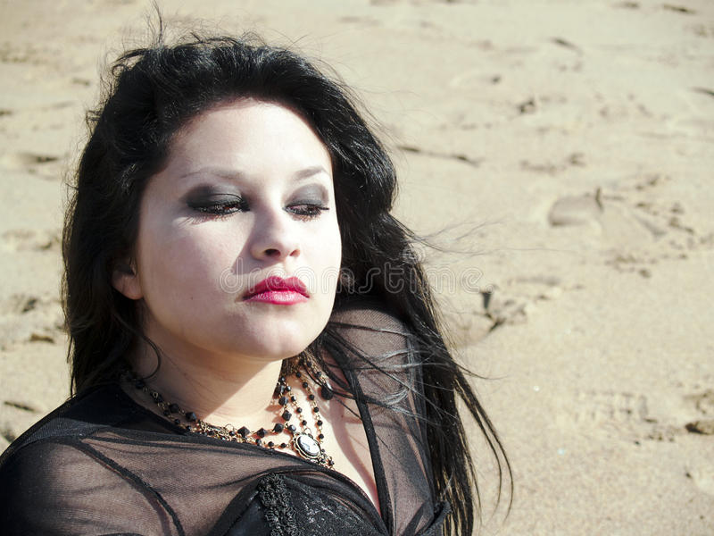 Young woman portraited on the sand. Gothic young woman posing outdoors at the seacoast of Valparaiso royalty free stock image