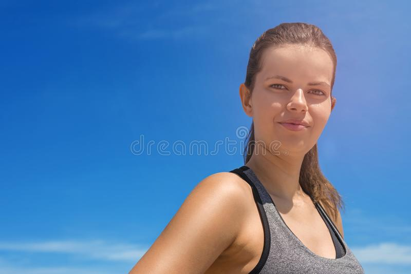 Young woman portriat in sportswear over blue sky in summer smiling. stock image