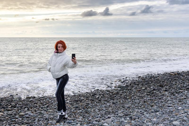 Young woman posing on a background of sea waves and sunset and making selfie royalty free stock photography