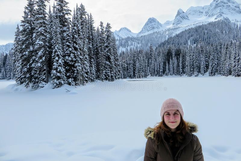 A young woman posing with the forests of Island Lake in Fernie, British Columbia, Canada behind. The majestic winter background is an absolutely beautiful stock images