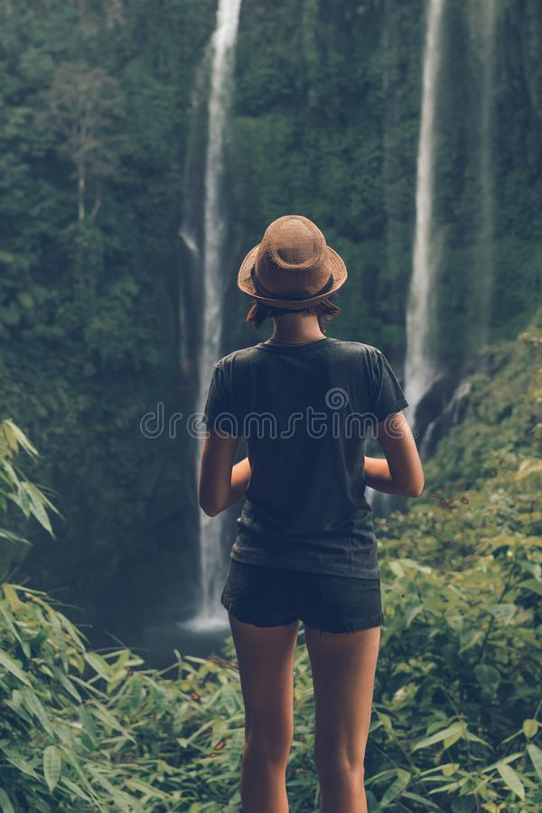 Young woman posing on a great Sekumpul waterfall in the deep rainforest of Bali island, Indonesia. Asia royalty free stock photography