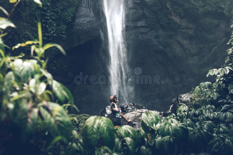 Young woman posing on a great Sekumpul waterfall in the deep rainforest of Bali island, Indonesia. Asia stock images