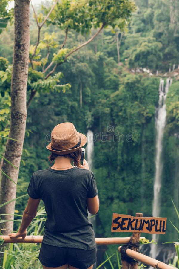 Young woman posing on a great Sekumpul waterfall in the deep rainforest of Bali island, Indonesia. Asia royalty free stock photo