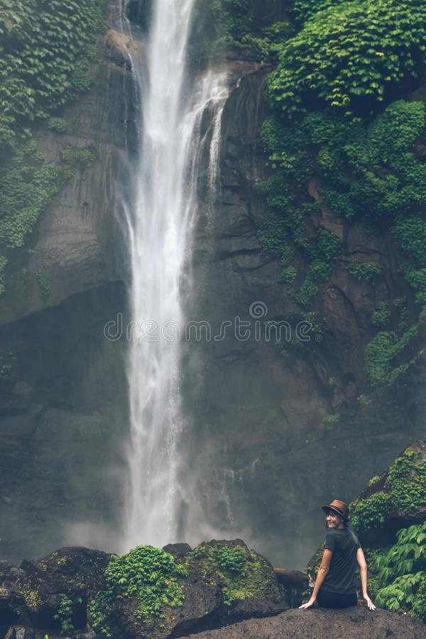 Young woman posing on a great Sekumpul waterfall in the deep rainforest of Bali island, Indonesia. Asia stock photo