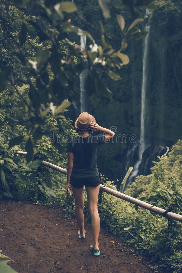 Young woman posing on a great Sekumpul waterfall in the deep rainforest of Bali island, Indonesia. Asia royalty free stock image