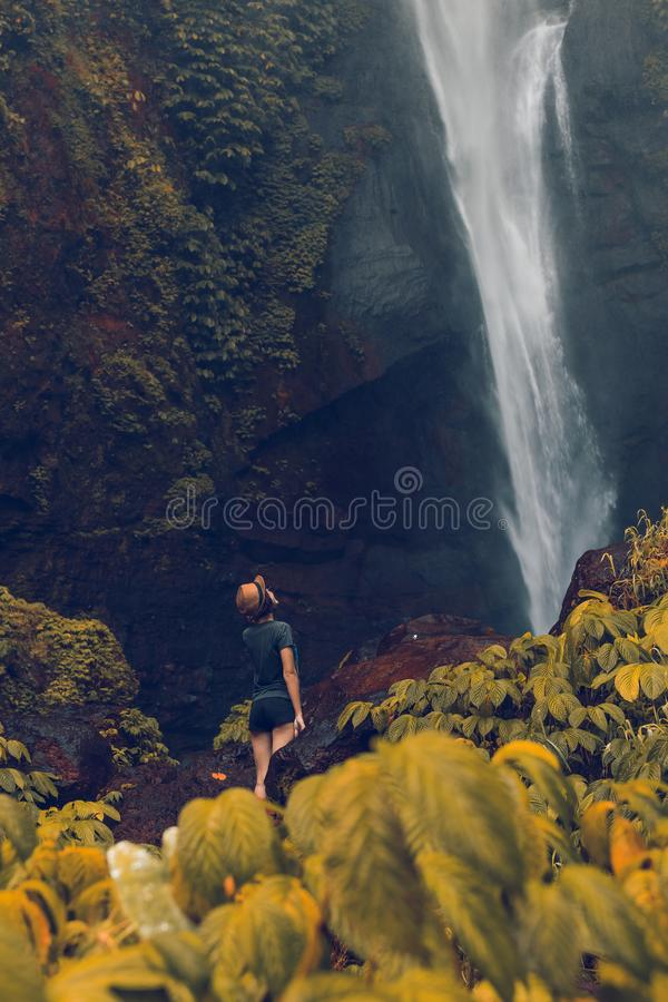 Young woman posing on a great Sekumpul waterfall in the deep rainforest of Bali island, Indonesia. Asia stock photography