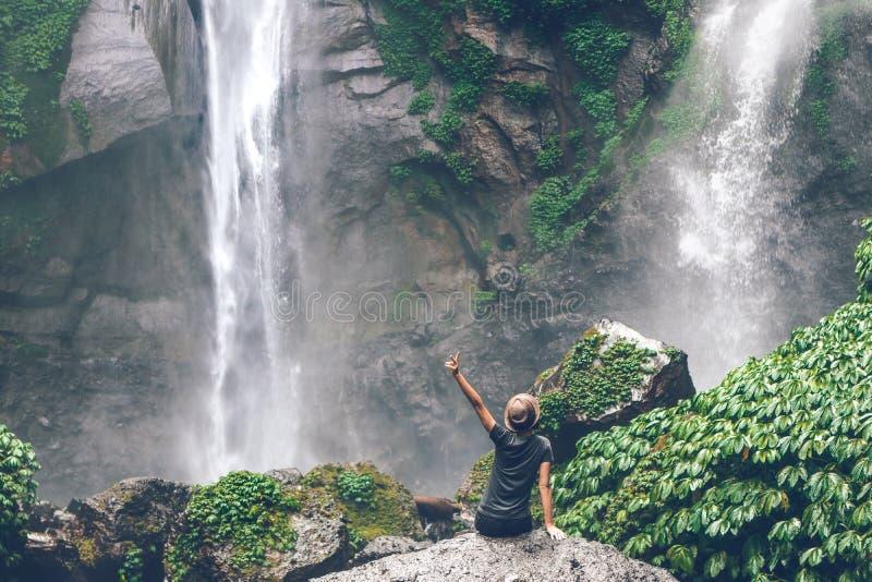 Young woman posing on a great Sekumpul waterfall in the deep rainforest of Bali island, Indonesia. Asia stock photos