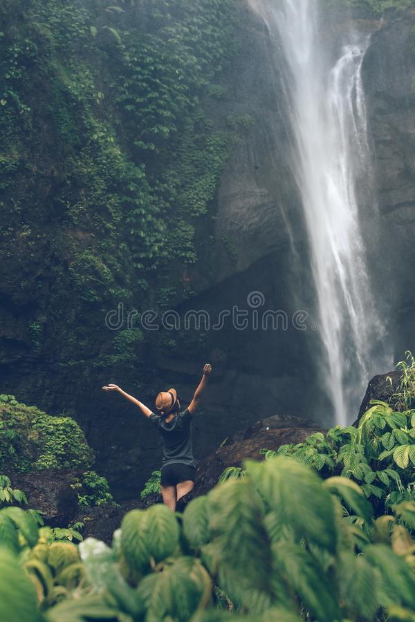 Young woman posing on a great Sekumpul waterfall in the deep rainforest of Bali island, Indonesia. Asia royalty free stock images
