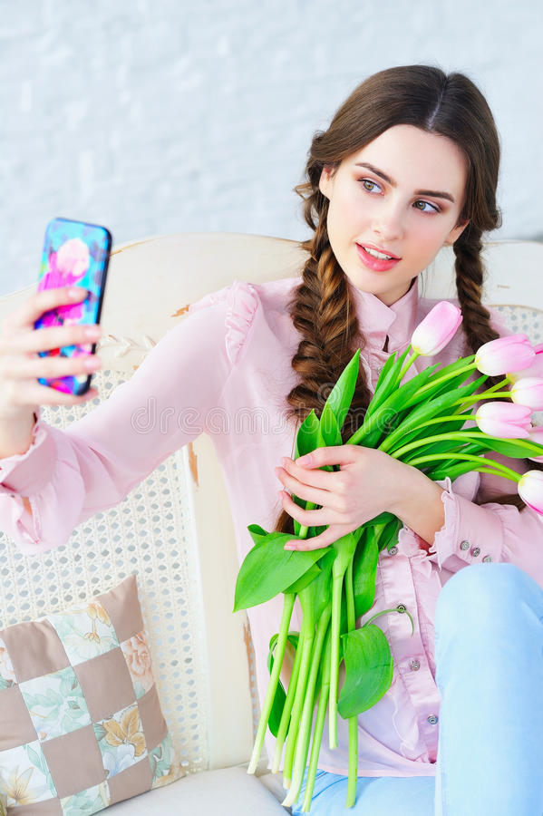 Young woman posing on her phone camera with flowers. Trendy young woman posing one her phone camera and taking photo of herself with bunch of spring pink flowers stock images