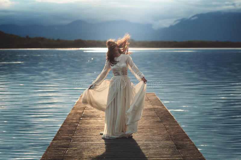 Young woman posing on lake pier. Dreamy light stock photos