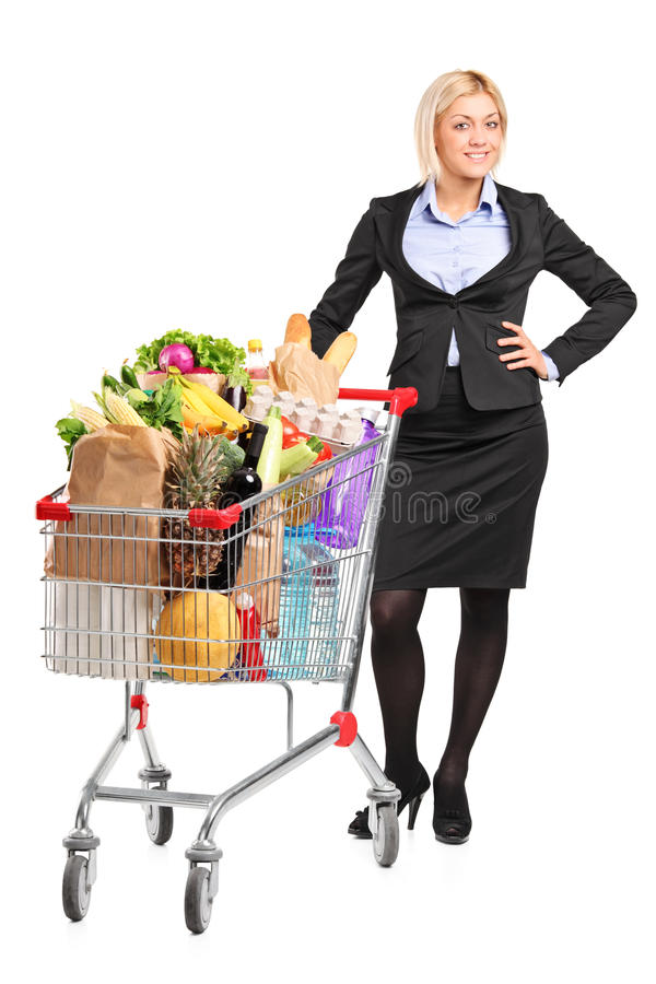 Young woman posing next to a shopping cart. Full length portrait of a young woman posing next to a shopping cart full with groceries on white background royalty free stock photos