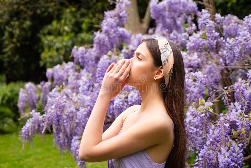 Young woman posing on a park background. Sneezing young girl with nose wiper among blooming trees in park. Pollen royalty free stock photography
