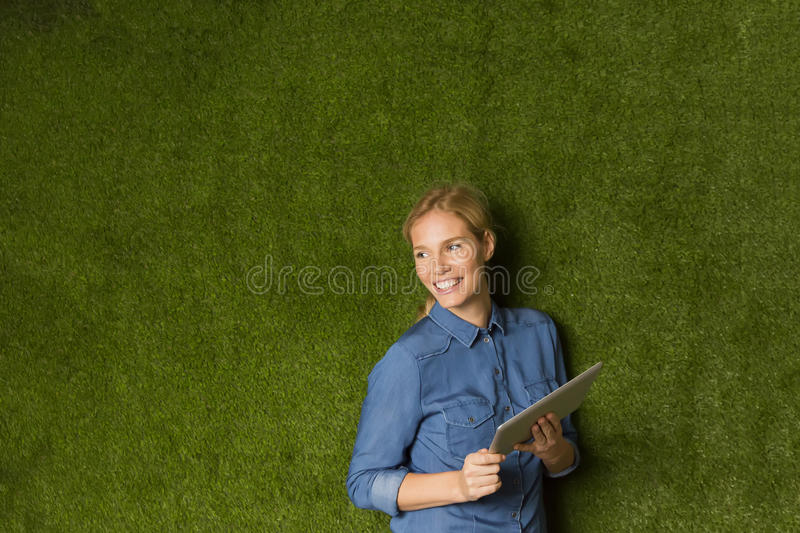 Young woman posing with tablet by green wall stock photography