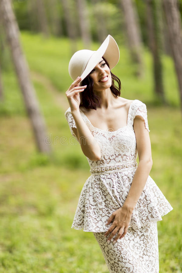 Young woman posing in a white dress with a hat royalty free stock images