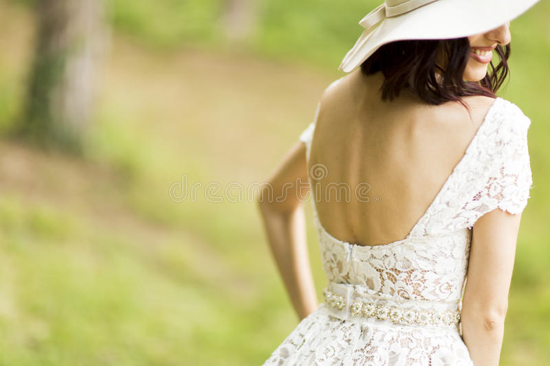 Young woman posing in a white dress with a hat stock image