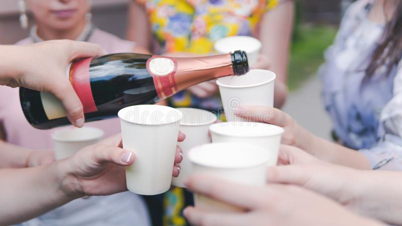 Young woman pouring champagne into glass, close-up outdoors. Young people celebrating with champagne at party outdoors stock images