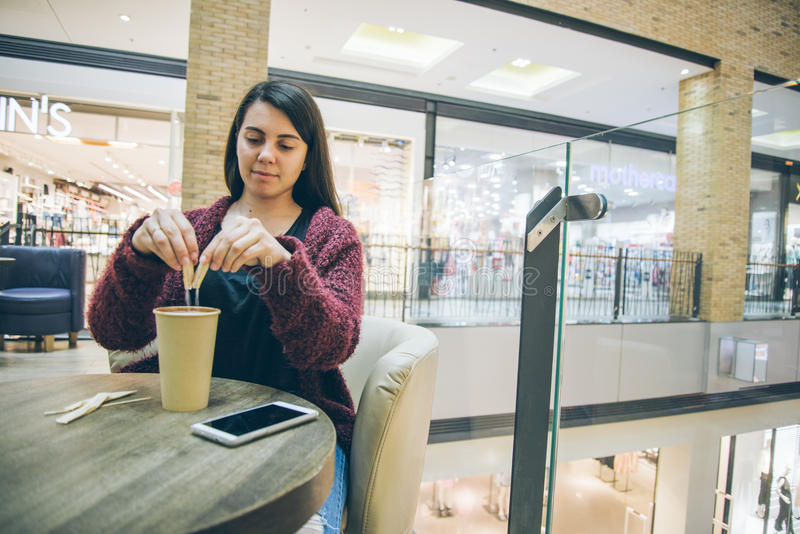 Young woman pouring sugar in coffe cup. In cafe stock images