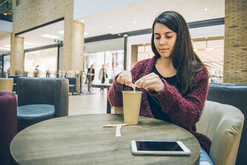 Young woman pouring sugar in coffe cup. In cafe stock image