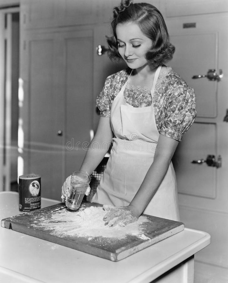 Young woman pouring water into flour stock photo