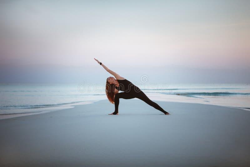 Summer yoga session on a beautiful golden beach of Maldives yoga tour, Extended Side Angle Pose Utthita Parsvakonasana. Young woman practice balance asanas on stock photo