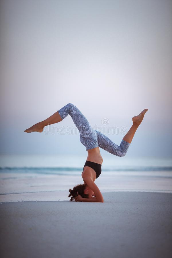 Summer yoga session on a beautiful golden beach of Maldives yoga tour, Salamba Sirsasana - supported headstand. Young woman practice balance asanas on Summer royalty free stock photography
