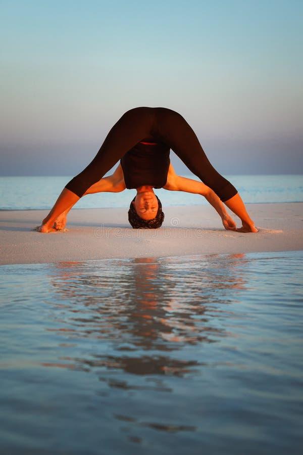 Summer yoga session on a beautiful golden beach of Wide-Legged Forward Bend - Prasarita Padottanasana I. Young woman practice balance asanas on Summer yoga royalty free stock photography