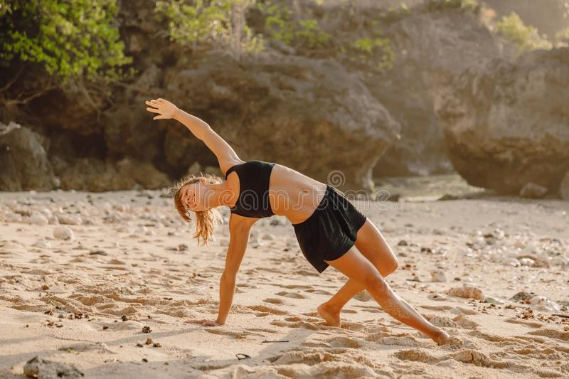 Young woman practice yoga at beach with sunset stock photography