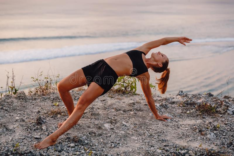 Young woman practice yoga at beach with sunset or sunrise stock image
