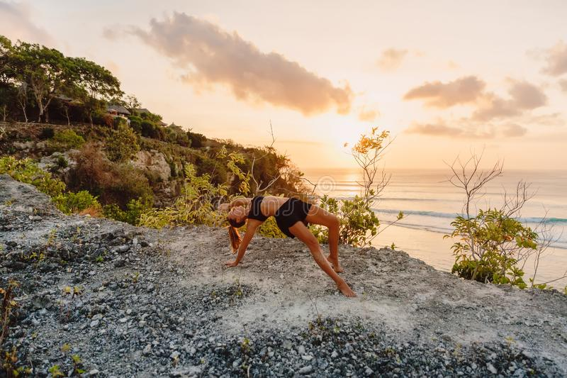 Young woman practice yoga at beach with sunset royalty free stock photo