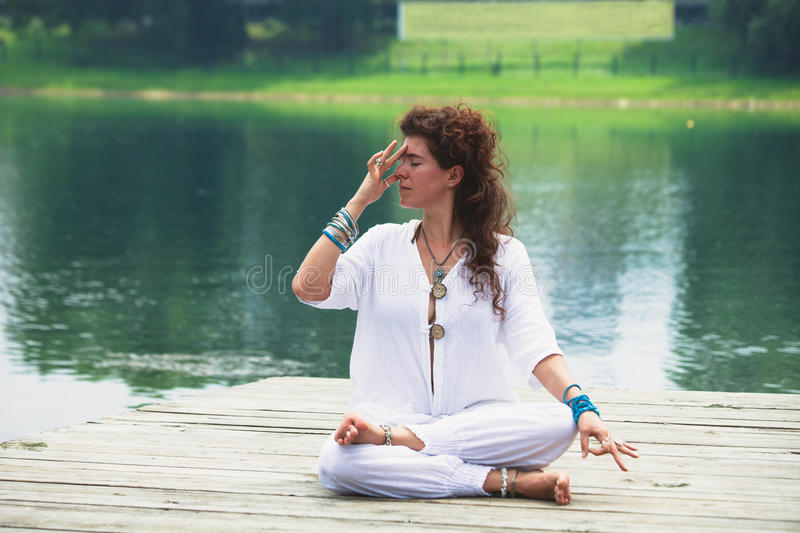 Young woman practice yoga breathing techniques outdoor. By the lake healthy lifestyle concept royalty free stock photography