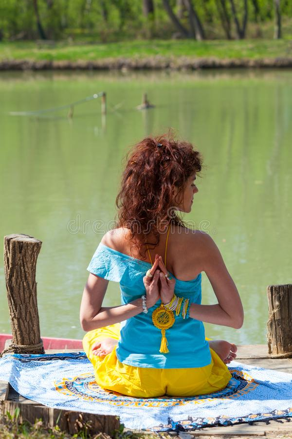 Young woman practice yoga outdoor by the lake healthy lifestyle concept back view full body shot. D royalty free stock photos