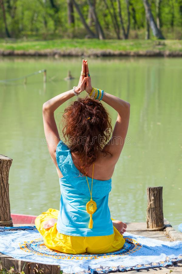 Young woman practice yoga outdoor by the lake healthy lifestyle concept back view full body shot. Hn royalty free stock images