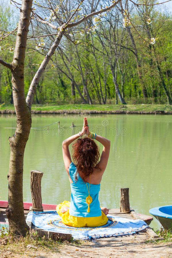 Young woman practice yoga outdoor by the lake healthy lifestyle concept back view full body shot. V royalty free stock images