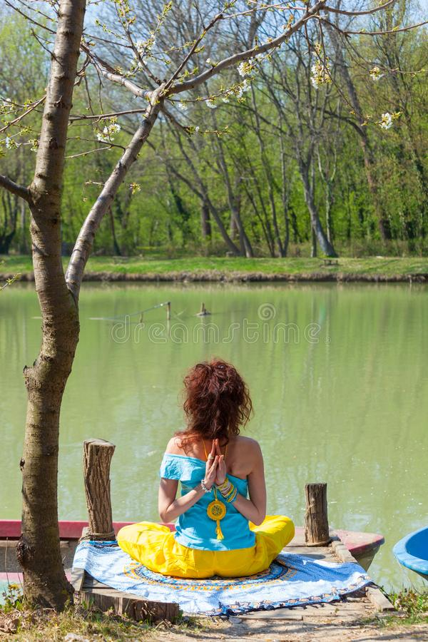Young woman practice yoga outdoor by the lake healthy lifestyle concept back view full body shot. J stock photo