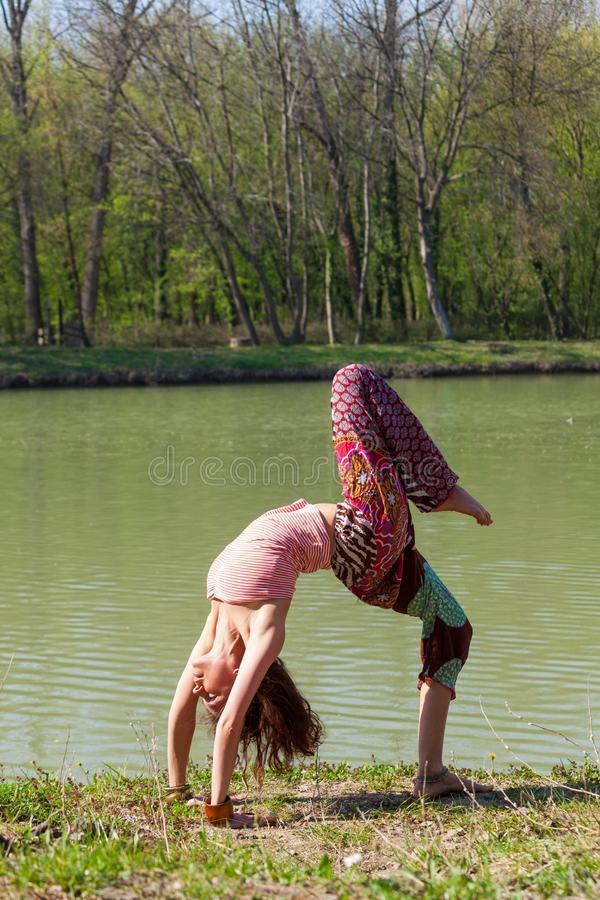 Young woman practice yoga outdoor by the lake healthy lifestyle concept full body shot royalty free stock photos