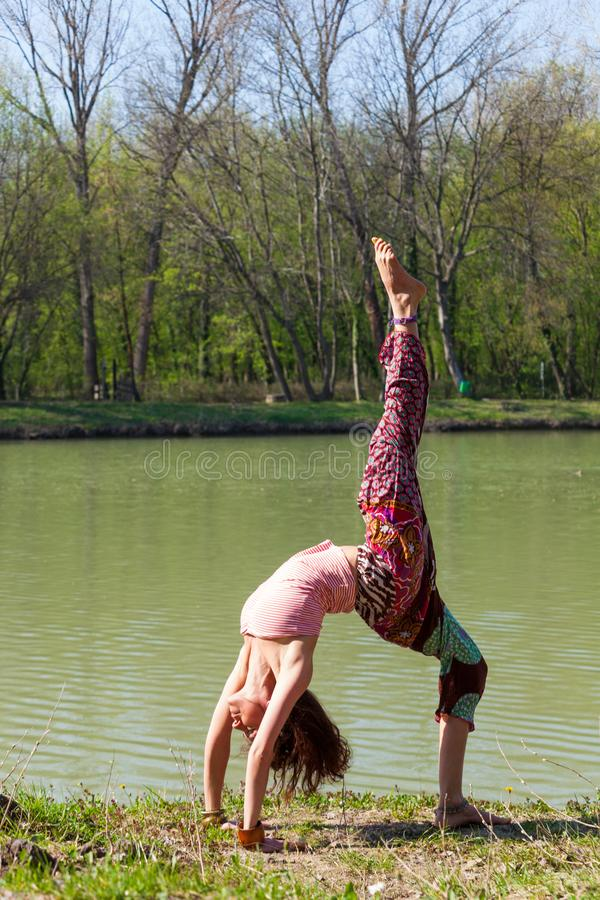 Young woman practice yoga outdoor by the lake healthy lifestyle concept full body shot royalty free stock photography