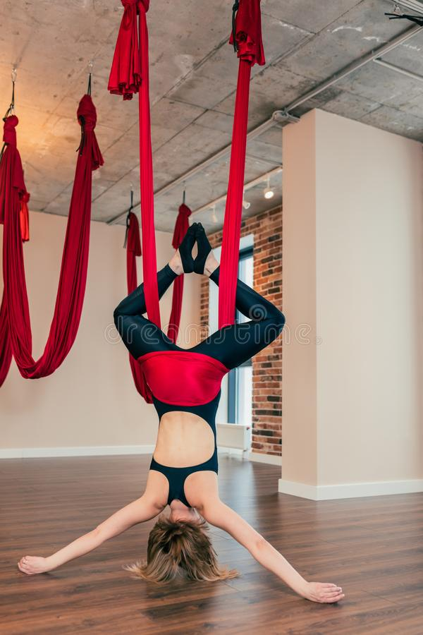 Blonde woman practices inversion anti-gravity yoga position, hanging upside down. Young woman practices aerial inversion anti-gravity yoga with a hammock in a stock images