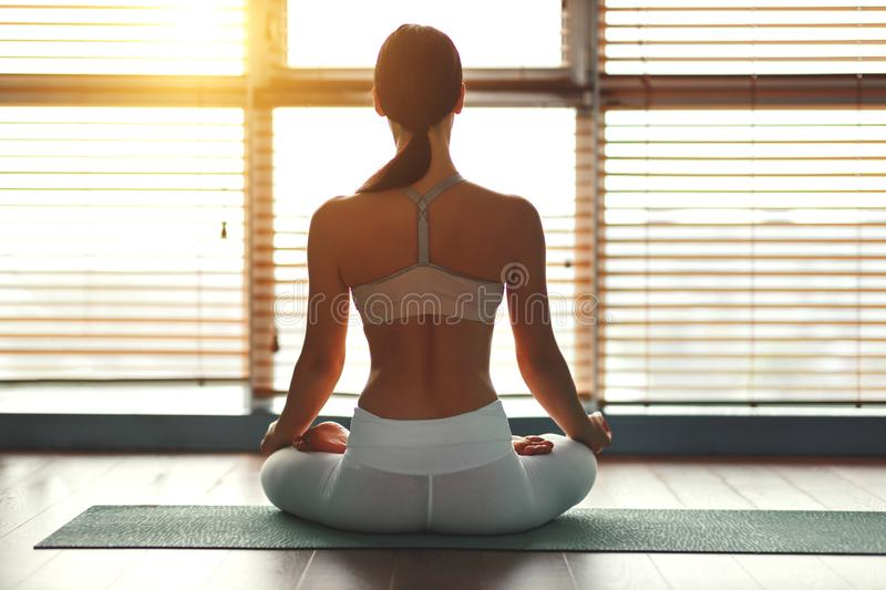 Young woman practices yoga at gym by window royalty free stock photos