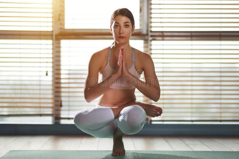 Young woman practices yoga at gym by window stock images