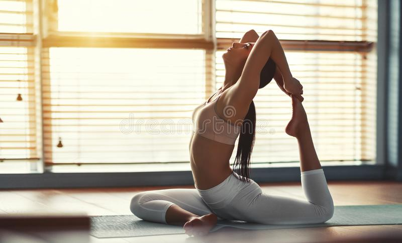 Young woman practices yoga at gym by window stock image