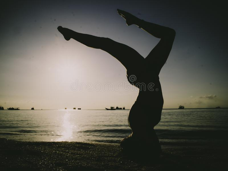 Silhouette Young Woman Practicing Yoga On The Beach At Sunset royalty free stock photo