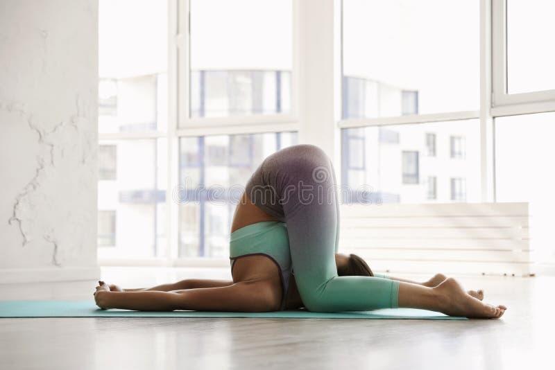 Young woman practicing deaf man`s asana in yoga studio stock photo