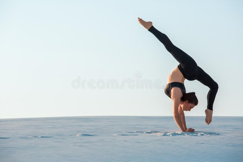 Young woman practicing inversion balancing yoga pose handstand on sand. Sunset and white sand royalty free stock images