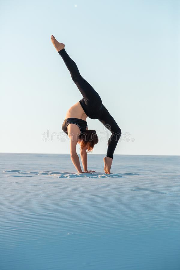 Young woman practicing inversion balancing yoga pose handstand on sand. Sunset and white sand stock photography