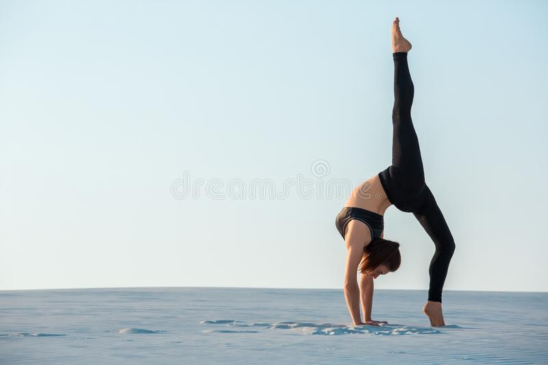 Young woman practicing inversion balancing yoga pose handstand on sand. Sunset and white sand royalty free stock photography