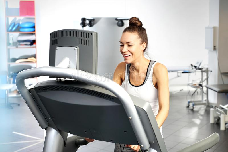 A young woman in an exercise room is running on an automatic treadmill. royalty free stock images
