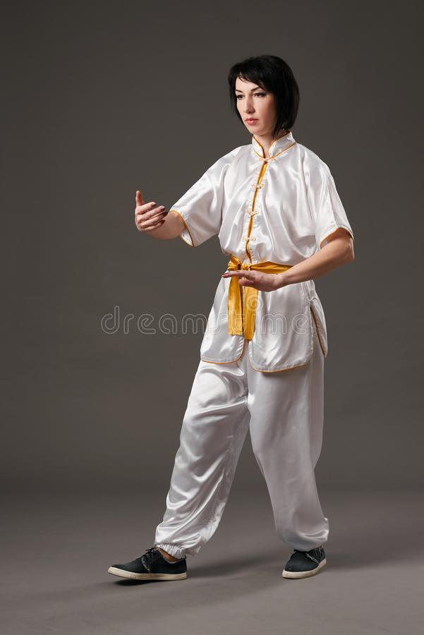 Young woman practicing tai chi chuan. Chinese management skill Qi`s energy. Gray background, studio shoot. stock photo
