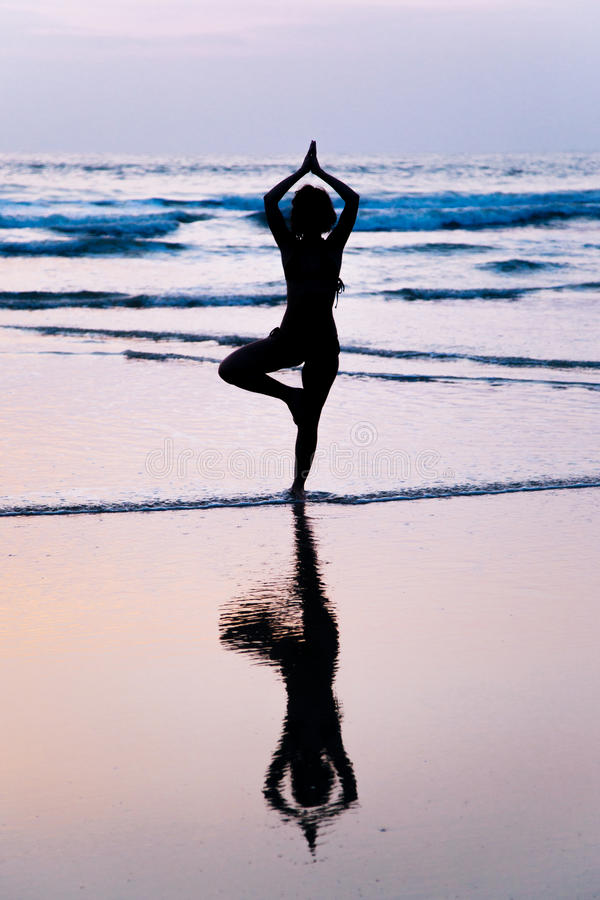 Young woman practicing yoga on beach in Agonda, India stock photos